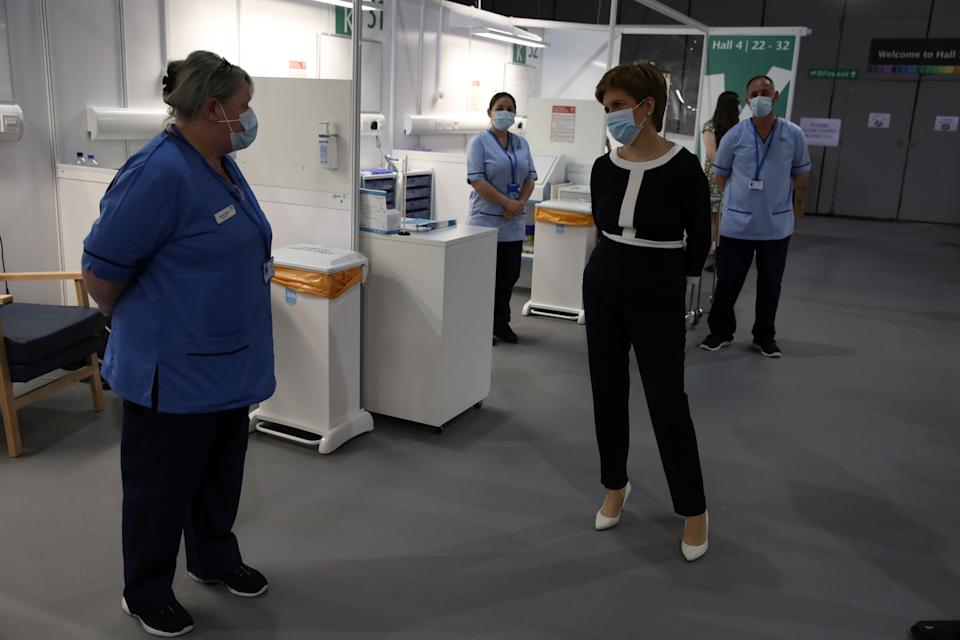 Scotland's First Minister Nicola Sturgeon (C) wears a face mask as she talks to nurses during her visit to the field hospital the NHS Louisa Jordan, set up at the SEC in Glasgow, Scotland on July 27, 2020, where she learned about how the venue, first setup to treat COVID-19 patients, is being adapted for to treat outpatients. (Photo by Andrew Milligan / POOL / AFP) (Photo by ANDREW MILLIGAN/POOL/AFP via Getty Images)