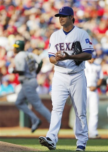 Texas Rangers pitcher Martin Perez, foreground, walks behind the mound while Oakland Athletics' Chris Carter, background, runs runs the bases after hitting a home run in the second inning of a baseball game Saturday, June 30, 2012, in Arlington, Texas. (AP Photo/Tim Sharp)