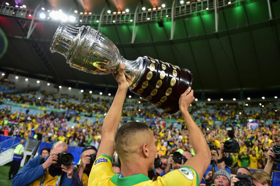 TOPSHOT - Brazil's Richarlison displays the trophy to the crowd after winning the Copa America by defeating Peru in the final match of the football tournament at Maracana Stadium in Rio de Janeiro, Brazil, on July 7, 2019. (Photo by Luis ACOSTA / AFP)        (Photo credit should read LUIS ACOSTA/AFP via Getty Images)