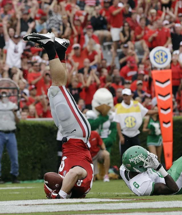 Georgia tight end Arthur Lynch (88) flps on his head after scoring on a touchdown on a pass from quarterback Aaron Murray as North Texas defensive back Hilbert Jackson (6) defends in the first half of an NCAA college football game Saturday, Sept. 21, 2013 in Athens, Ga. (AP Photo/John Bazemore)