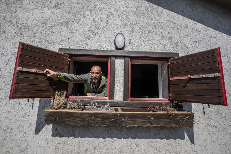 """In this image take on Friday, April 24, 2020 Claudio Trentani, 57, opens a window of his shelter 'Baita Cassinelli' (1568 Mt.), at the foot of Mt. Presolana, in Castione della Presolana, near Bergamo, northern Italy. Of the COVID-19 pandemic he says, """"It is a powerful tragedy that has touched chords that not even during the war had been touched.""""  (AP Photo/Luca Bruno),"""