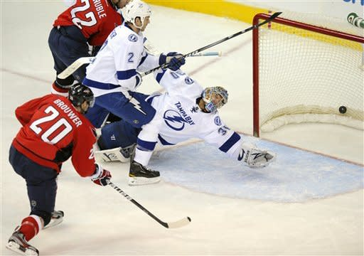 Washington Capitals left wing Troy Brouwer (20) scores a goal pastinst Tampa Bay Lightning goalie Dwayne Roloson (30) and Eric Brewer (2) during the second period of an NHL hockey game, Friday, Jan. 13, 2012, in Washington. (AP Photo/Nick Wass)