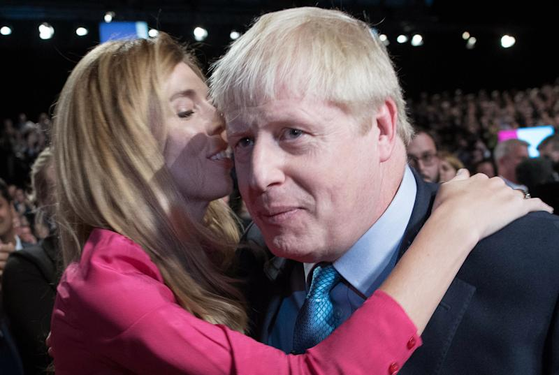"Britain's Prime Minister Boris Johnson (R) is embraced by his partner Carrie Symonds as they leave after he delivered his keynote speech to delegates on the final day of the annual Conservative Party conference at the Manchester Central convention complex, in Manchester, north-west England on October 2, 2019. - Prime Minister Boris Johnson was set to unveil his plan for a new Brexit deal at his Conservative party conference Wednesday, warning the EU it is that or Britain leaves with no agreement this month. Downing Street said Johnson would give details of a ""fair and reasonable compromise"" in his closing address to the gathering in Manchester, and would table the plans in Brussels the same day. (Photo by Stefan Rousseau / POOL / AFP) (Photo by STEFAN ROUSSEAU/POOL/AFP via Getty Images)"