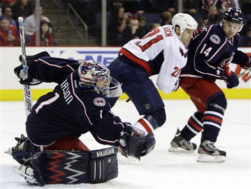 Columbus Blue Jackets goalie Steve Mason (1) makes a save as Grant Clitsome (14) and Washington Capitals' Brooks Laich (21) look for the rebound during the first period of an NHL hockey game, Saturday, Dec. 31, 2011, in Columbus, Ohio. (AP Photo/Jay LaPrete)