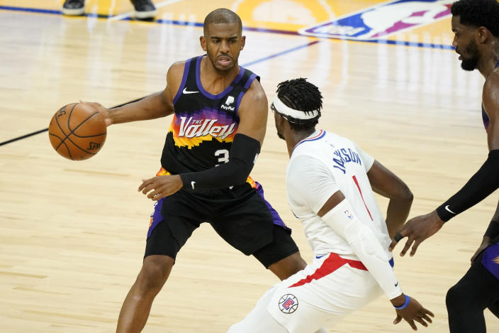 Phoenix Suns guard Chris Paul looks to pass as Los Angeles Clippers guard Reggie Jackson, right, defends during the first half of game 5 of the NBA basketball Western Conference Finals, Monday, June 28, 2021, in Phoenix. (AP Photo/Matt York)