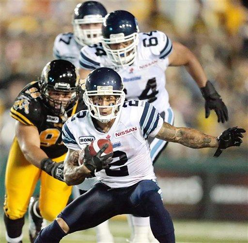 Toronto Argonauts' Chad Owens avoids a tackle from Hamilton Tiger-Cats' Eddie Steele, left, during their 36-27 loss to the Ti-Cats in their Canadian Football League game at Ivor Wynne Stadium in Hamilton, Ontario, Saturday, July 14, 2012. (AP Photo/The Canadian Press, Geoff Robins)