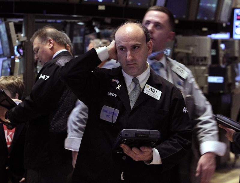 In an April 23, 2012 photo, trader Andrew Silverman, center, works on the floor of the New York Stock Exchange Monday, April 23, 2012.  Wall Street appeared headed for a slightly higher open Thursday, April 26, 2012 with Dow Jones industrial futures rising 0.1 percent and S&P 500 futures up 0.1 percent  (AP Photo/Richard Drew)