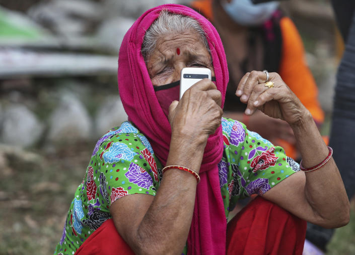 A woman wearing face mask as a precaution against the coronavirus talks on the mobile phone as she waits to get tested for COVID-19 in Jammu, India, Wednesday, May 12, 2021. Misinformation about the coronavirus is surging in India as the death toll from COVID-19 rises. Fueled by anguish, distrust and political polarization, the claims are further compounding India's crisis. (AP Photo/Channi Anand)