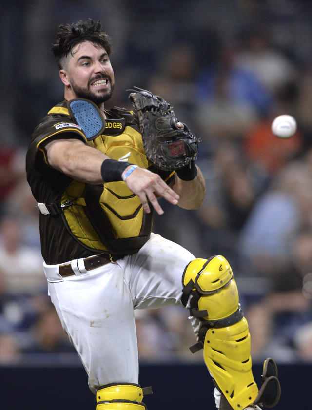 San Diego Padres catcher Austin Hedges throws to first base late on a wild pitch swinging strike-out by San Francisco Giants' Austin Slater during the sixth inning of a baseball game Friday, July 26, 2019, in San Diego. (AP Photo/Orlando Ramirez)