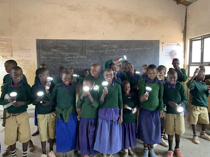 Tanzanian schoolchildren hold up solar flashlights charged using the miraculous Solar Cow.