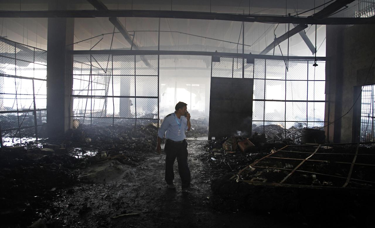 An airline employee stands in a warehouse gutted by fire at the Jinnah International Airport Pakistan, Tuesday, June 10, 2014. Pakistani airport authorities found seven bodies in a burned building at the Karachi international airport on Tuesday, bringing the death toll from the attack there to at least 35, including the 10 Taliban attackers, officials said. (AP Photo/Shakil Adil)