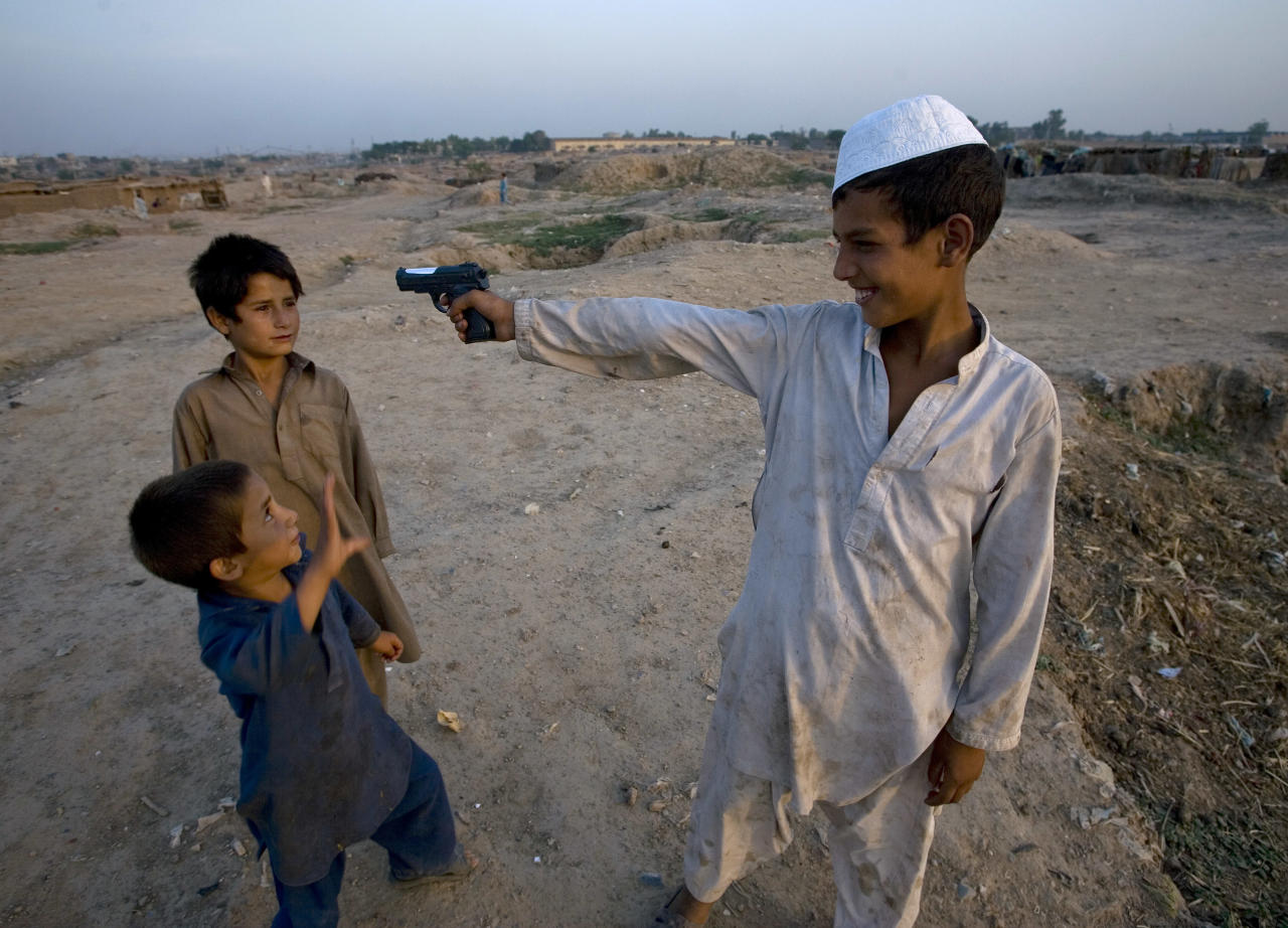 An Afghan refugee boy aims a toy gun at other boy as they playing in a slum on the outskirts of Islamabad, Pakistan, Sunday, June 19, 2011. World Refugee Day will be marked on Monday, June 20. (AP Photo/Anjum Naveed)