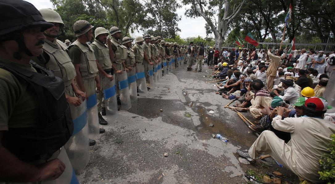 Pakistani troops stand guard as supporters of anti-government Muslim cleric Tahir-ul-Qadri stage a sit in protest close to Prime Minister's home in Islamabad, Pakistan on Monday, Sept. 1, 2014. Anti-government protesters and Pakistani police have clashed once again as the demonstrators pushed into a sprawling government complex in the country's capital in an effort to try to reach the prime minister's official residence. (AP Photo/Anjum Naveed)