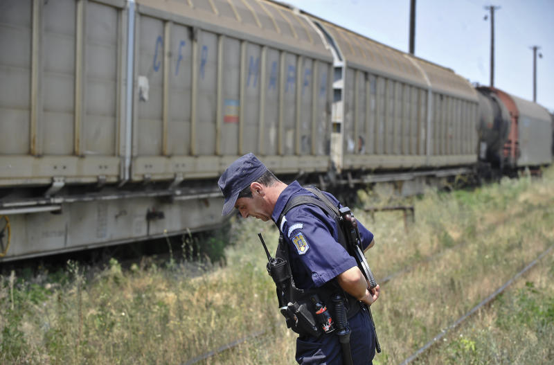 In this image taken on Sunday, July 17, 2011 a Romanian gendarme stands next to a freight train that was transporting Romanian produced weapons to Bulgaria in Giurgiu, southern Romania. Authorities say they are investigating the theft of 64 missile warheads from the train transporting military equipment to Bulgaria. Interior ministry spokesman Marius Militaru said Sunday the components are not dangerous on their own  only when integrated into missile systems. Railway workers on Saturday noticed the seals on a carriage door were broken, and it was not properly closed when the train reached Giurgiu, a Danube port that borders Bulgaria.(AP Photo/Bogdan Stamatin)