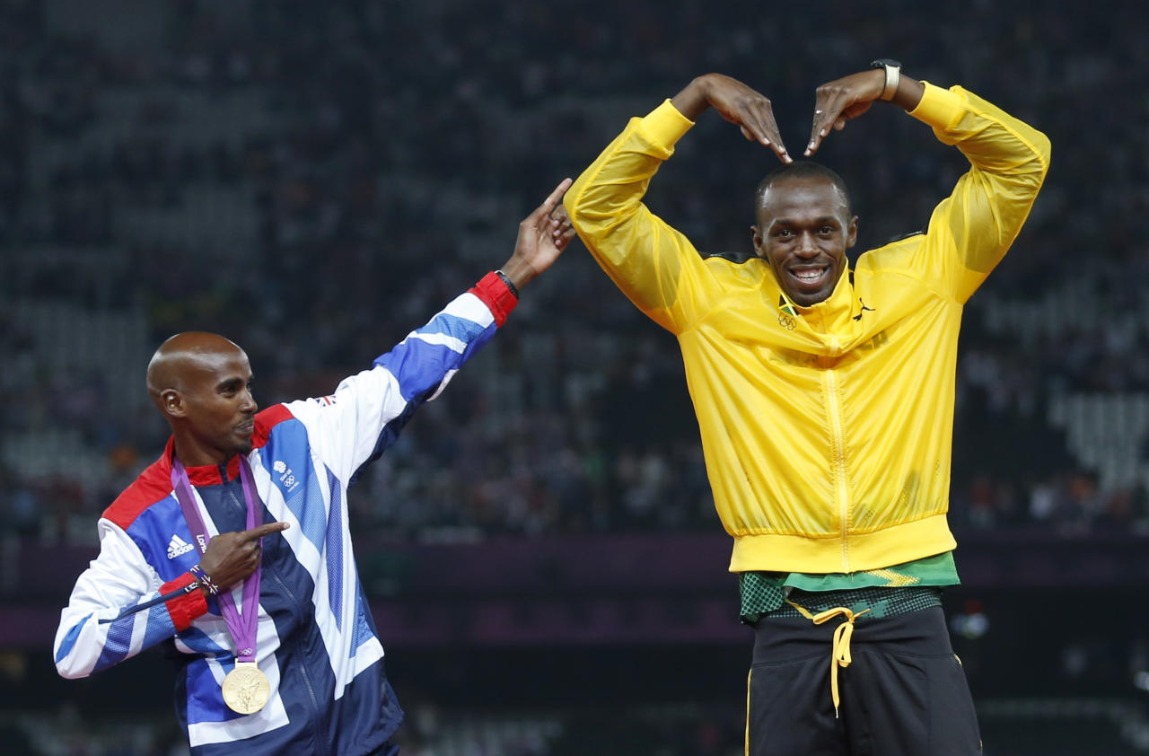 Jamaica's Usain Bolt (R) celebrates with Britain's Mo Farah on the podium after each receiving gold medals, Bolt for men's 4x100m relay and Farah for men's 5000m at the victory ceremony at the London 2012 Olympic Games at the Olympic Stadium August 11, 2012.          REUTERS/Eddie Keogh (BRITAIN  - Tags: SPORT OLYMPICS SPORT ATHLETICS TPX IMAGES OF THE DAY)