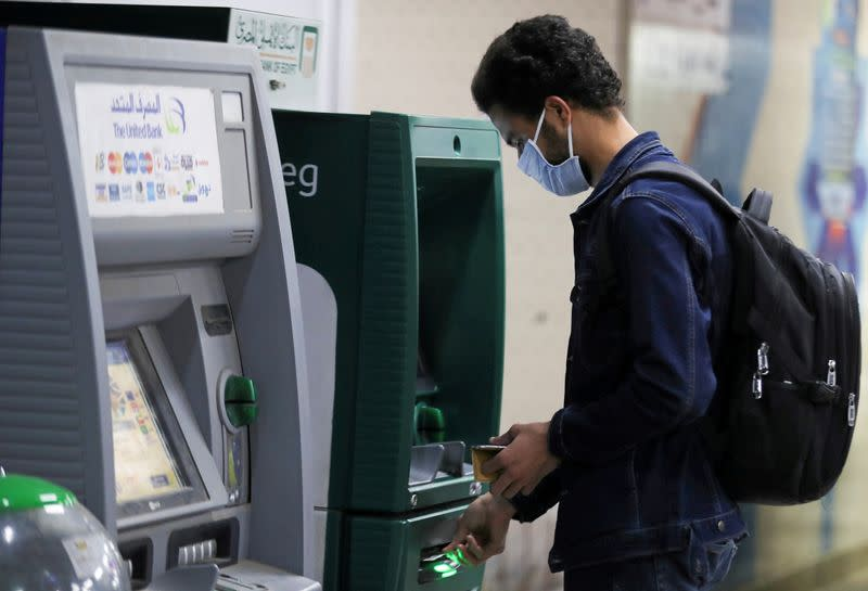 FILE PHOTO: A man wearing a protective face mask withdraws money from an ATM in Cairo