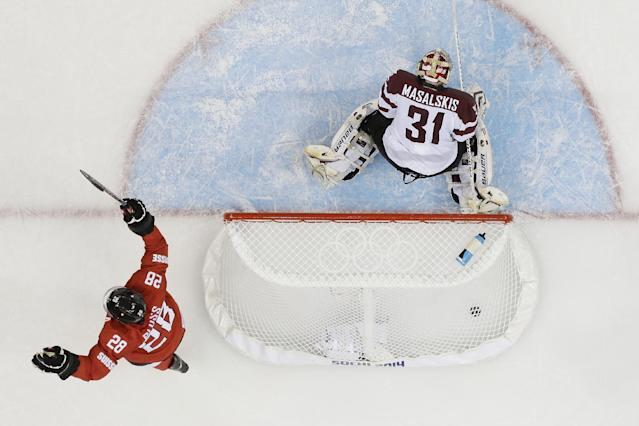 Latvia goaltender Edgars Masalskis looks down at the ice as Switzerland forward Martin Pluss celebrates the winning goal by Switzerland forward Simon Moser during the closing seconds of the 2014 Winter Olympics men's ice hockey game at Shayba Arena, Wednesday, Feb. 12, 2014, in Sochi, Russia. (AP Photo/Matt Slocum)