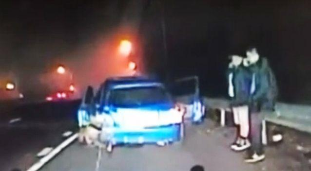 The two men were assessing damage from a previous crash when the second car roared into shot. Photo: Screenshot