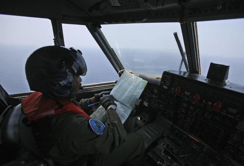 """An Indonesian Navy pilot checks his map during a search operation for the missing Malaysian Airlines Boeing 777 over the waters bordering Indonesia, Malaysia and Thailand near the Malacca straits on Monday, March 10, 2014. Dozens of ships and aircraft have failed to find any piece of the missing Boeing 777 jet that vanished more than two days ago above waters south of Vietnam as investigators pursued """"every angle"""" to explain its disappearance, including hijacking, Malaysia's civil aviation chief said Monday. (AP Photo/Binsar Bakkara)"""