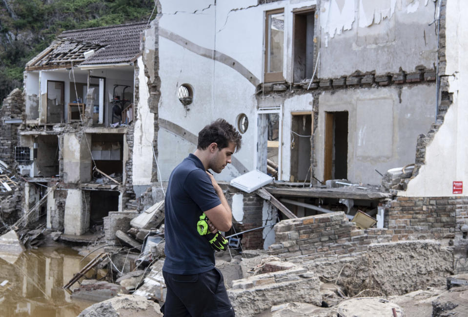A fireman walks in front of completely destroyed houses in the village of Mayschoß, Germany, Tuesday, July 20, 2021. Numerous houses in the village were badly affected or completely swept away by the flood wave.( Boris Roessler/dpa via AP)