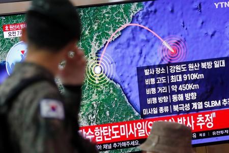 A South Korean soldier walks past a TV broadcasting a news report on North Korea firing a missile that is believed to be launched from a submarine, in Seoul