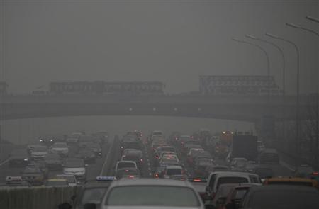 Cars drive on and below Guomao Bridge on a heavily hazy day in Beijing