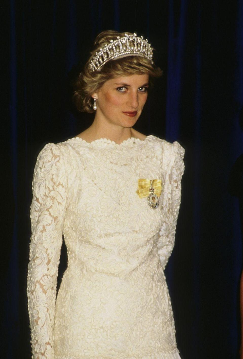 <p>On a visit to Vancouver, Canada, Diana chose a white long-sleeved lace gown. She paired the delicate dress with the Cambridge Lover's Knot tiara, matching pearl drop earrings, and her Royal Order. (The Lover's Knot was so heavy it hurt Diana's head, but it remained one of her favorites regardless.)</p>