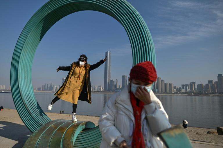 A woman poses for a photo in a park along the Yangtze River in Wuhan in China's central Hubei province