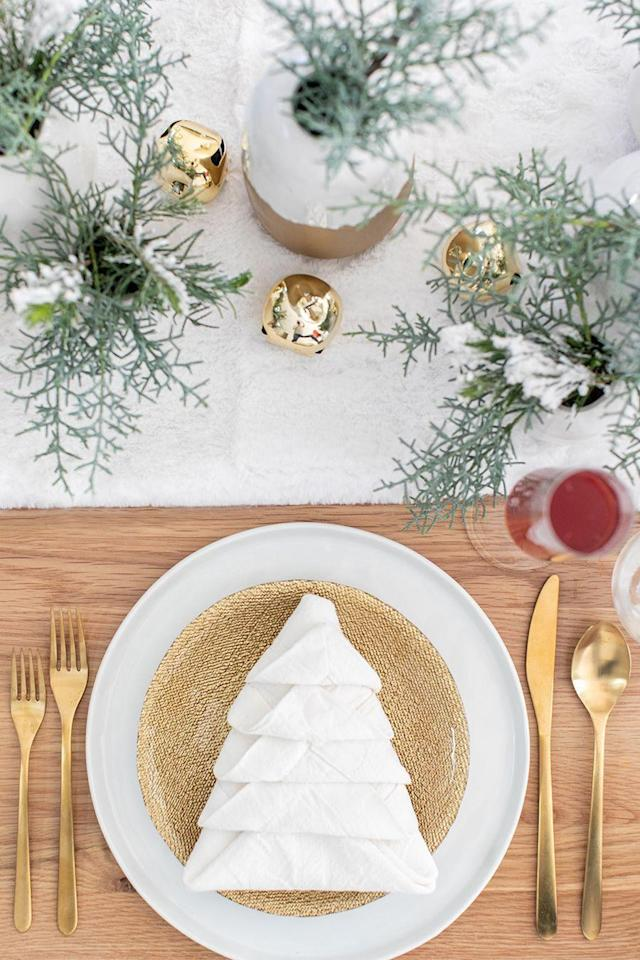 """<p>Wow your guests with this stunning Christmas tree napkin! Believe it or not, it's super easy to pull off—you just need a few large linen napkins to get started.</p><p><strong>Get the tutorial at <a href=""""https://sugarandcharm.com/how-to-put-together-a-charming-christmas-brunch"""" rel=""""nofollow noopener"""" target=""""_blank"""" data-ylk=""""slk:Sugar and Charm"""" class=""""link rapid-noclick-resp"""">Sugar and Charm</a>.</strong></p><p><strong><a class=""""link rapid-noclick-resp"""" href=""""https://www.amazon.com/Berglander-Flatware-Stainless-Titanium-Silverware/dp/B07536QR2Y?tag=syn-yahoo-20&ascsubtag=%5Bartid%7C10050.g.644%5Bsrc%7Cyahoo-us"""" rel=""""nofollow noopener"""" target=""""_blank"""" data-ylk=""""slk:SHOP GOLD FLATWARE"""">SHOP GOLD FLATWARE</a></strong></p>"""
