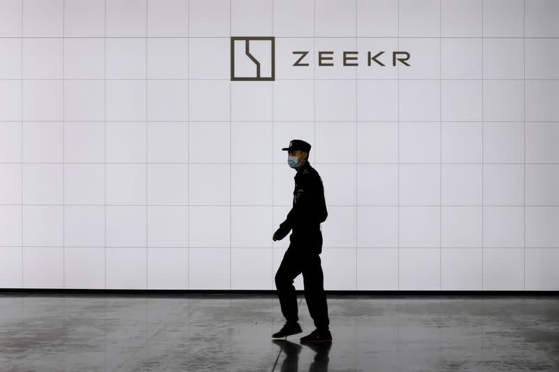 Security guard walks past a sign of Geely's new brand Zeekr at its factory in Ningbo