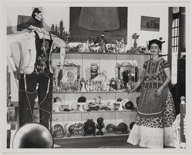Frida Kahlo in Rivera's living room with figure of Judas, circa 1940. On view at the MFA, Boston.