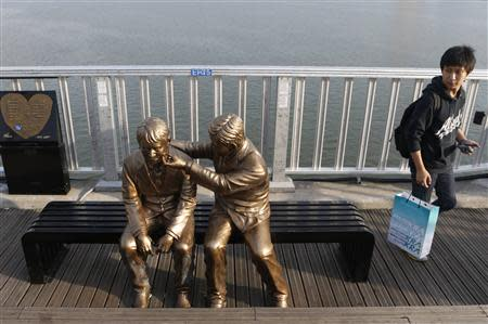 A man walks past a statue of a person comforting another on the Mapo Bridge in central Seoul