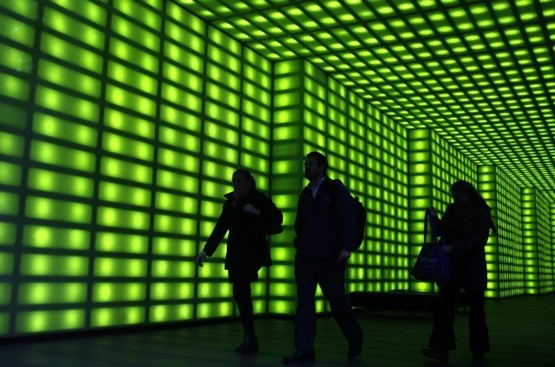Office workers walk through a green lit foyer of an office building in Melbourne