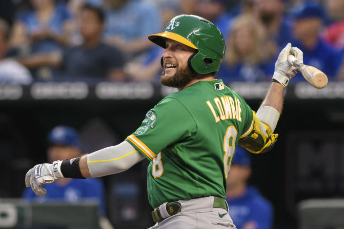 Oakland Athletics' Jed Lowrie hits a sacrifice fly to score teammate Starling Marte during the first inning of a baseball game against the Kansas City Royals, Tuesday, Sept. 14, 2021 in Kansas City, Mo. (AP Photo/Reed Hoffmann)