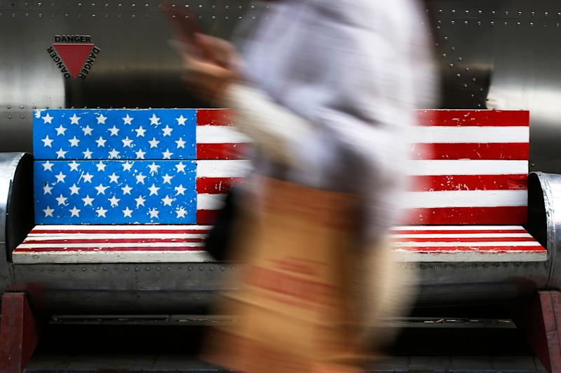 In this Sunday, Jan. 6, 2019, photo, a woman walks by a bench painted with the U.S. flag at the capital city's popular shopping mall in Beijing. A U.S. delegation led by deputy U.S. trade representative, Jeffrey D. Gerrish arrived in the Chinese capital for a trade talks with China. China sounded a positive note ahead of trade talks this week with Washington, but the two sides face potentially lengthy wrangling over technology and the future of their economic relationship. (AP Photo/Andy Wong)