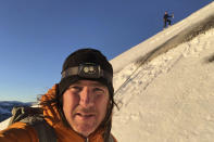 """In this photo provided by Jason Torlano, he poses with his friend, Zach Milligan, right, on their descent down Half Dome in Yosemite National Park, Calif., on Sunday, Feb. 21, 2021. Two men climbed some 4,000 feet to the top of Yosemite's Half Dome in subfreezing temperatures and skied down the famously steep monolith to the valley floor. Torlano, 45, and Milligan, 40, completed the daring descent in five hours on Sunday by charging down Half Dome's arching back and using ropes to rappel down several sections of bare rock known as the """"death slabs,"""" the Fresno Bee reported on Thursday. (Jason Torlano via AP)"""