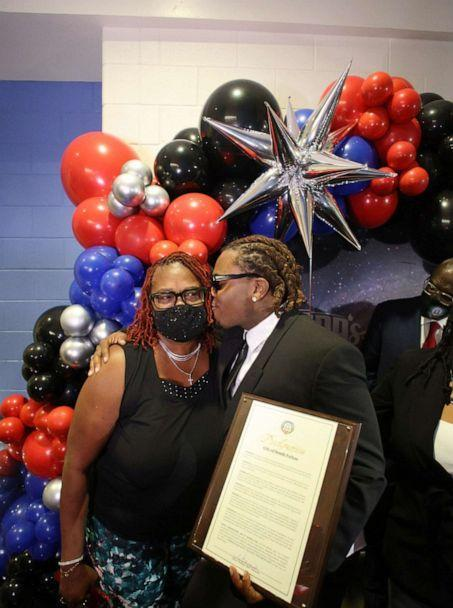 PHOTO: Hip-hop artist Gunnar kisses his mom at the grand opening of Gunna's Drip Closet and Goodr Grocery Store at McNair Middle School on Sept. 16, 2021. (Maurice Holloway/Goodr)
