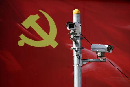 Security cameras are attached to a pole in front of a party flag of Communist Party of China in Shanghai, China September 14, 2017. REUTERS/Aly Song