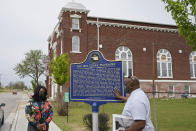 """Chief Egunwale Amusan, right, and Tiffany Crutcher, left, talk about a sign commemorating the original Black Wall Street while on a tour given by Amusan, in Tulsa, Okla., on Monday, April 12, 2021. Crutcher says, terrorized by the Tulsa Race Massacre, """"My father's grandmother, Rebecca Brown Crutcher, had to flee Greenwood in fear of her life."""" But the family stayed in Tulsa, enduring some of the same post-massacre hardships that generations of Black Tulsans endured: urban renewal, inequality on the north side and police brutality. (AP Photo/Sue Ogrocki)"""