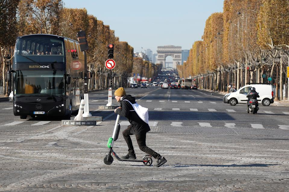 A man passes by the Champs Elysees avenue as he rides a dock-free electric scooter Lime-S by California-based bicycle and scooter sharing service Lime, in Paris, France, November 9, 2018. REUTERS/Charles Platiau