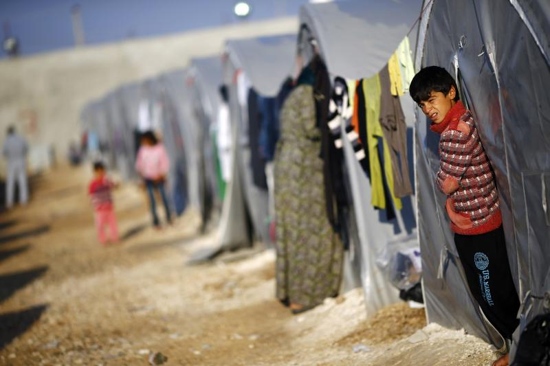 A Kurdish refugee boy from the Syrian town of Kobani stands outside his tent in a camp in the southeastern town of Suruc