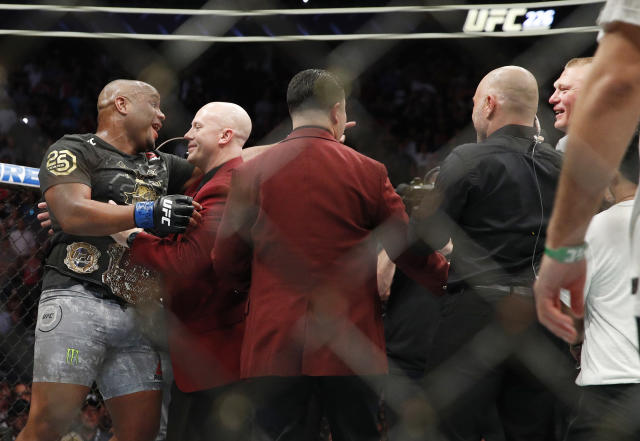 Brock Lesnar, right, taunts Daniel Cormier, left, after Cormier's heavyweight title mixed martial arts bout at against Stipe Miocic at UFC 226, Saturday, July 7, 2018, in Las Vegas. (AP Photo/John Locher)