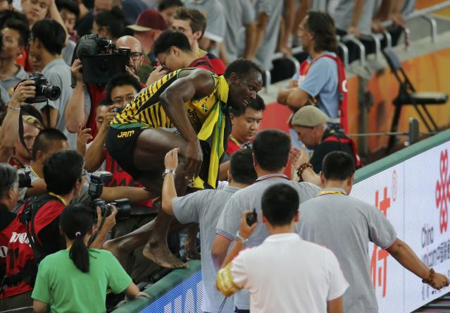 Usain Bolt of Jamaica jumps across an advertising hoarding after winning the men's 200 metres final during the 15th IAAF World Championships at the National Stadium in Beijing