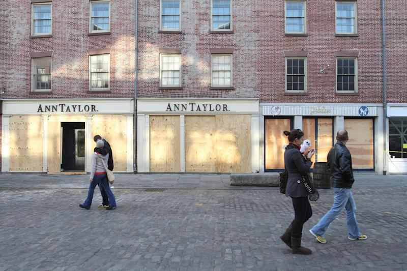 In this Friday, Nov. 23, 2012 photo, people walk past boarded up shops at New York's South Street Seaport. The South Street Seaport, a popular tourist destination, remains a ghost town since Superstorm Sandy. (AP Photo/Tina Fineberg)