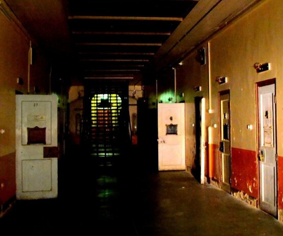 An interior image of Adelaide Gaol with crumbling painted walls and open, unhinged doors.