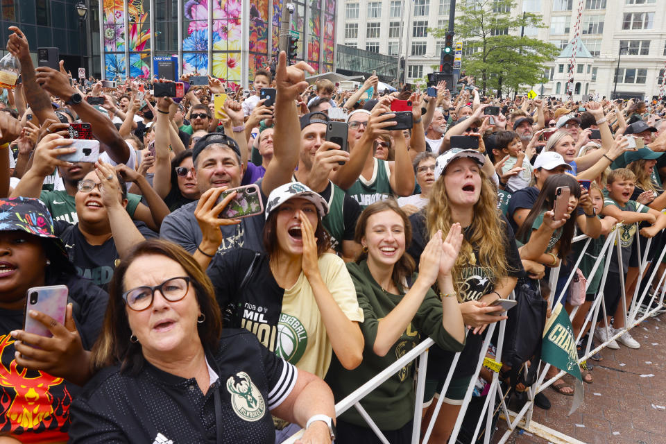 Fans scream for players on buses during a parade and celebration for the NBA Championship Bucks basketball team Thursday, July 22, 2021, in Milwaukee. (AP Photo/Jeffrey Phelps)
