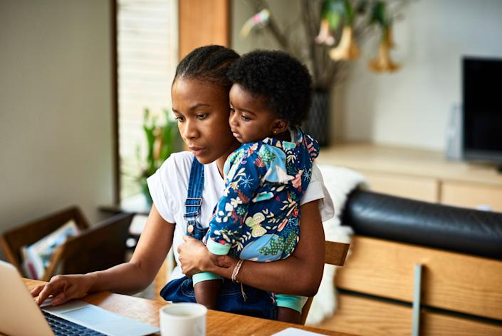 Woman with baby son (6-11 months) working on laptop at home (Photo: 10'000 Hours via Getty Images)