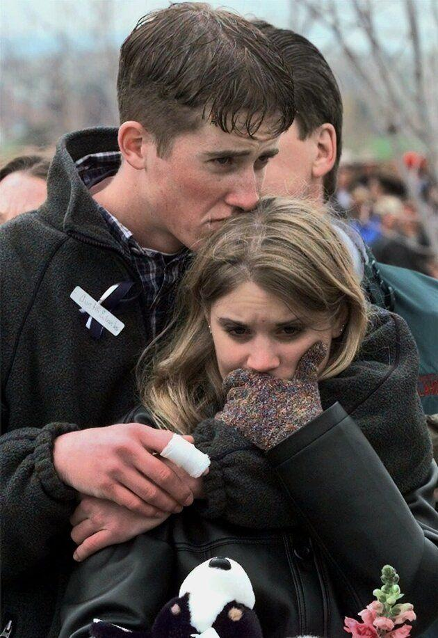 In this April 25, 1999 photo, Columbine High School shooting victim Austin Eubanks hugs his girlfriend during a memorial service in Littleton, Colorado. Thirteen people were killed by two gunmen, students at the school who then died by suicide.