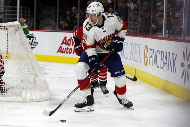 FILE - In this Dec. 21, 2019, file photo, Florida Panthers' Mark Pysyk (13) moves the puck away from Carolina Hurricanes' Sebastian Aho (20) during the third period of an NHL hockey game in Raleigh, N.C. New York Rangers' Brendan Smith and Pysyk are the latest to follow the lead of Hall of Famers Red Kelly and Mark Howe and present-day Brent Burns and Dustin Byfuglien, and their experience could open the door for more multiposition players in a sport that usually defines being a center, winger or defenseman very specifically. (AP Photo/Karl B DeBlaker, File)