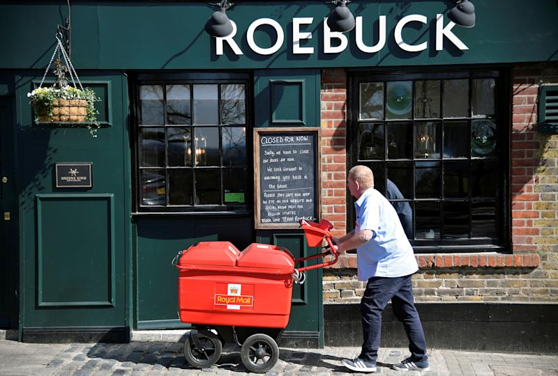 "A Royal Mail delivery man looks at a ""Closed"" sign on a pub as he does his rounds, as the spread of the coronavirus disease (COVID-19) continues, in Richmond, London, Britain, March 24, 2020. REUTERS//Toby Melville"